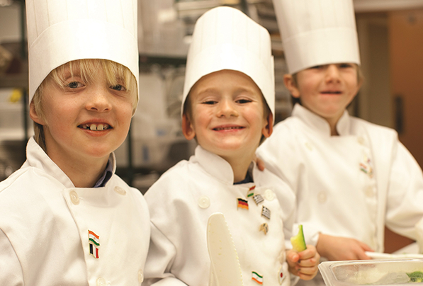 Little kids dressed as chefs enjoy the camp activities at The Sebastian - Vail.