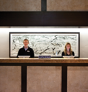 Concierge desk staff smile to welcome new arrivals to The Sebastian Hotel in Vail.