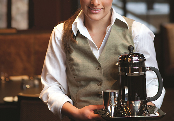 A smiling female server brings coffee to hotel guests in Vail Village.