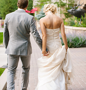 A happy bride and groom hold hands and walk together after marrying.