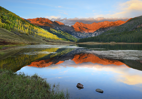 A glittering lake sits at the foot of stunning mountains in Vail.