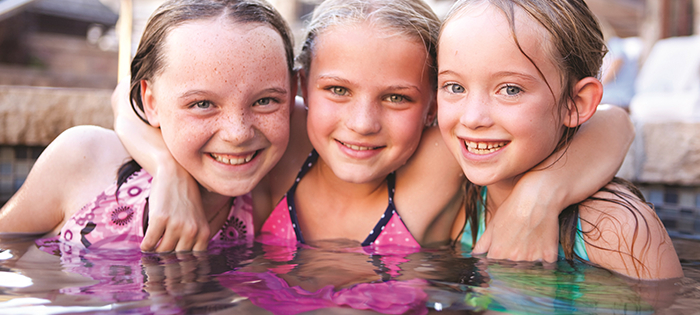 Three kids smile while playing in the hotel pool.