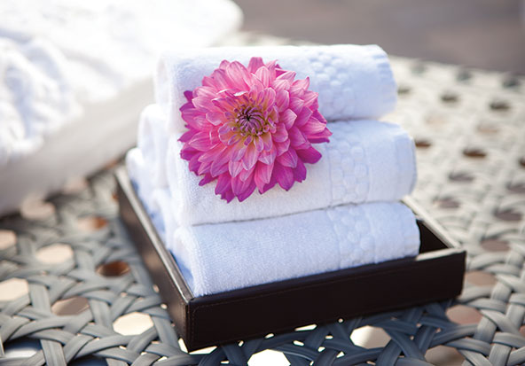 A bottle of massage oil and towels sits on a table at Bloom Spa