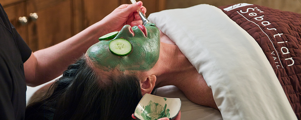A relaxed and peaceful woman enjoys a facial at Bloom Spa.