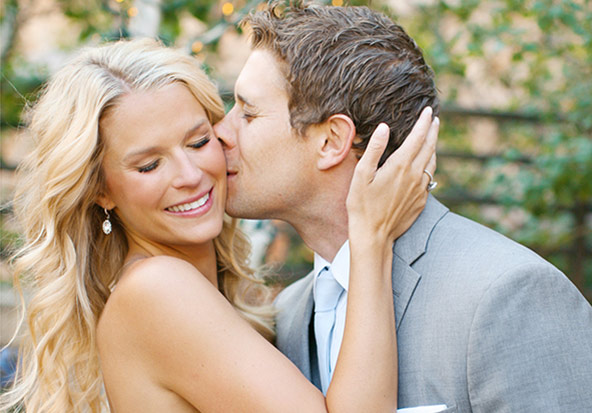 A handsome groom kisses his smiling and equally beautiful bride at their wedding.
