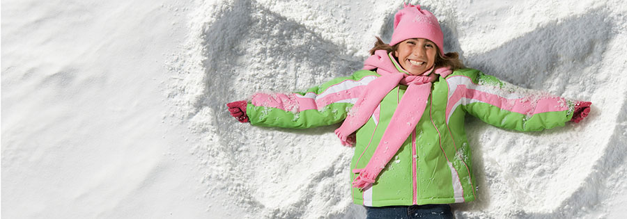 A young girl makes a snow angel while visiting The Sebastian - Vail hotel.