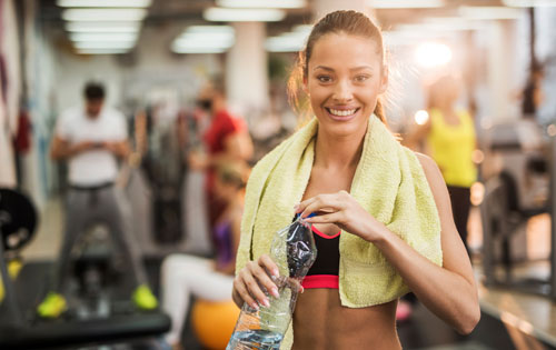 A pretty, healthy woman takes a sip of water during a workout.
