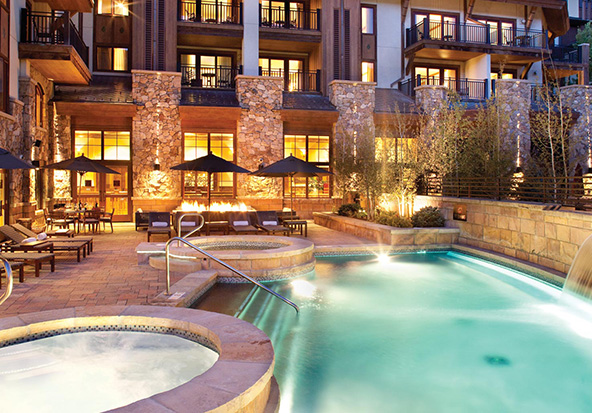 The spa's pool and hot tub at The Sebastian - Vail sits under a night sky.