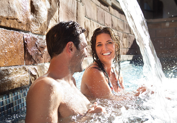 A beautiful couple from Vail sit in the hotel pool under a waterfall.