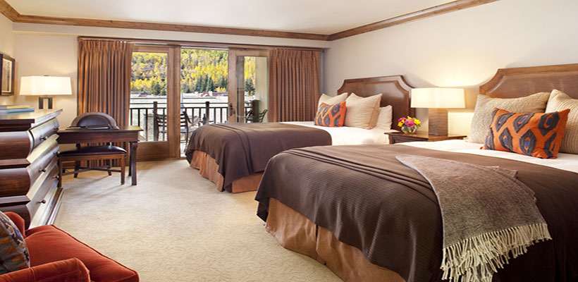 Two beds sit next to an open window with a beautiful view of Vail.