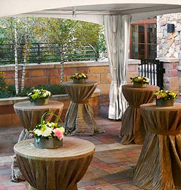 Tables with baskets of flowers stand ready for wedding guests.