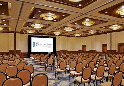 A large Colorado event venue with a projector holds dozens of chairs in neat rows.
