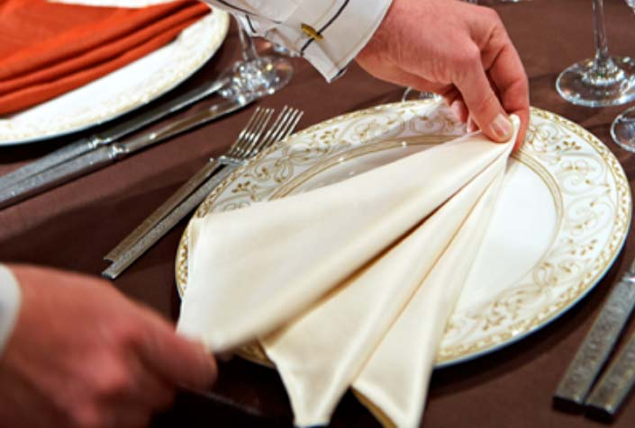 A server meticulously folds a napkin for a wedding.