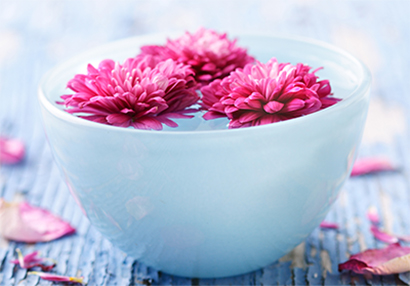 Gorgeous, pink flowers float in a white bowl of water.