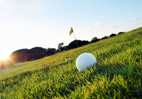 A golf ball sits on trimmed grass with the pin flag in the background.