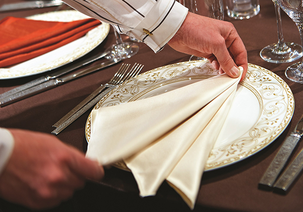 A server beautifully folds a napkin on a table.