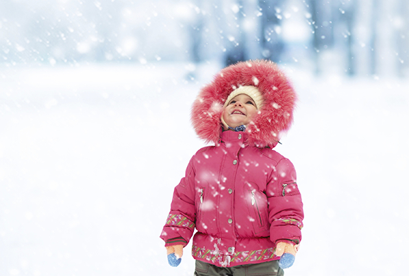 A kid in a pink coat looks at snow at The Sebastian Hotel in Vail.