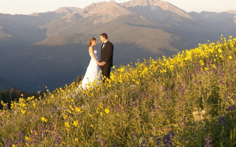 A wedding couple holds hands outdoors during their Colorado mountain wedding in Vail.
