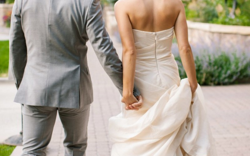 A newlywed couple holds hands at The Sebastian's wedding venue in Colorado.
