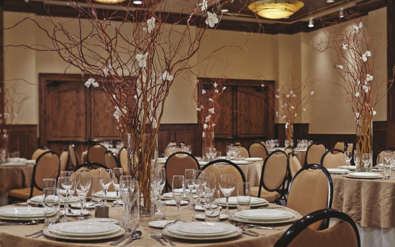 The ballroom at The Sebastian Vail hotel is set up with tables and centerpieces for a Vail wedding.