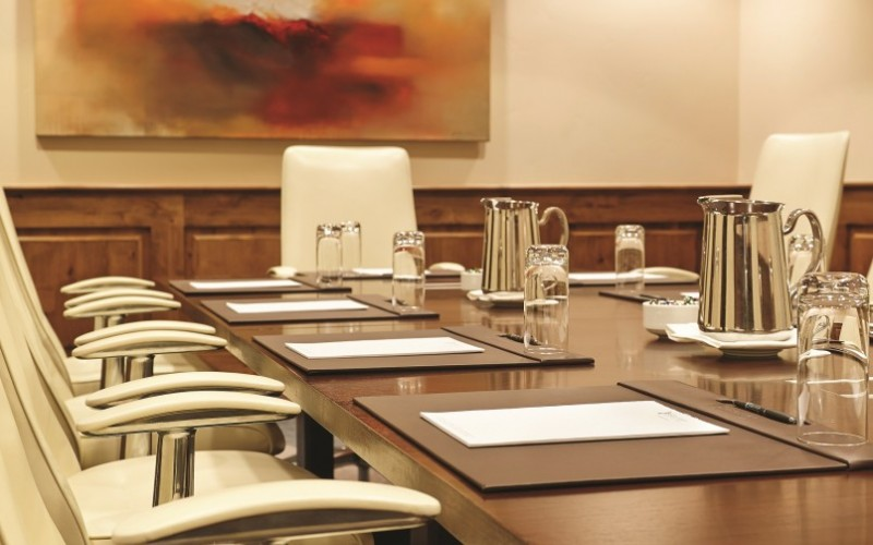 The Magellan Board Room at The Sebastian Vail is set up for a Colorado meeting with note pads, pens and water glasses.