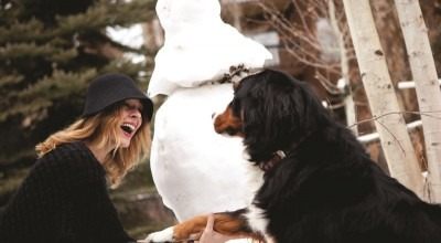 woman with dog building snowman in Vail village